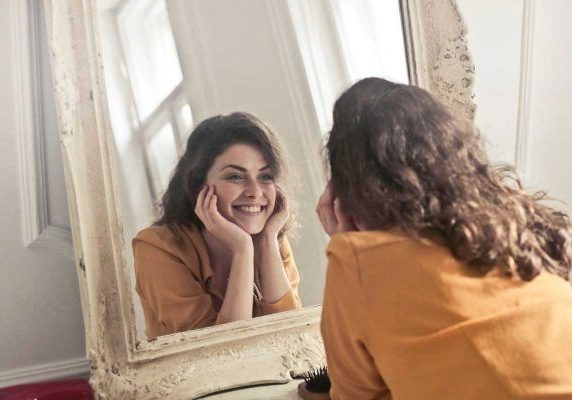 Happy-woman-looking-in-mirror